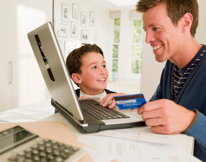 A smiling man holds a credit card and looks at his computer while a boy looks on smiling.