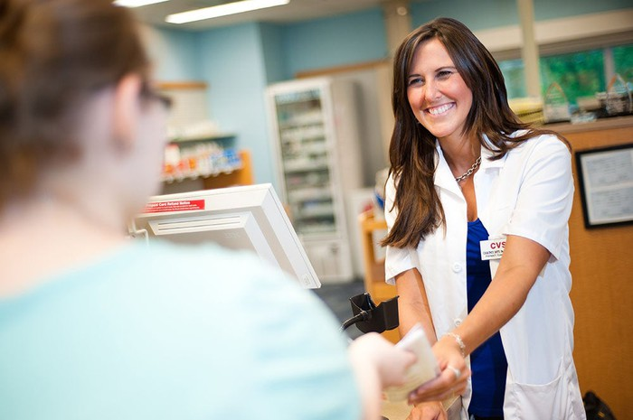 Female CVS pharmacist at counter helping patient