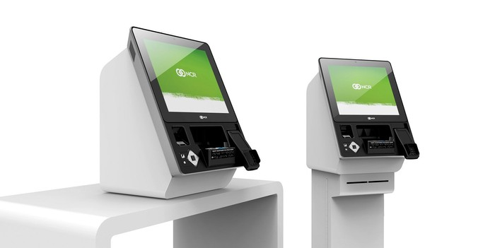 Two kiosks with NCR logos on the screen, sitting on white pedestal and desk.