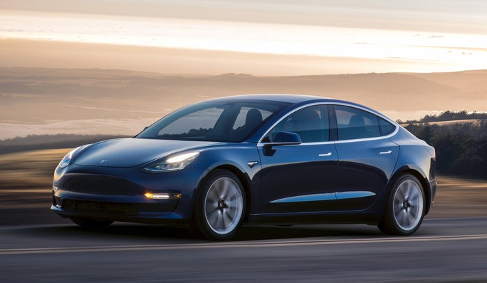 A dark blue Tesla Model 3, a sleek compact luxury sports sedan, on a beach road at sunset.