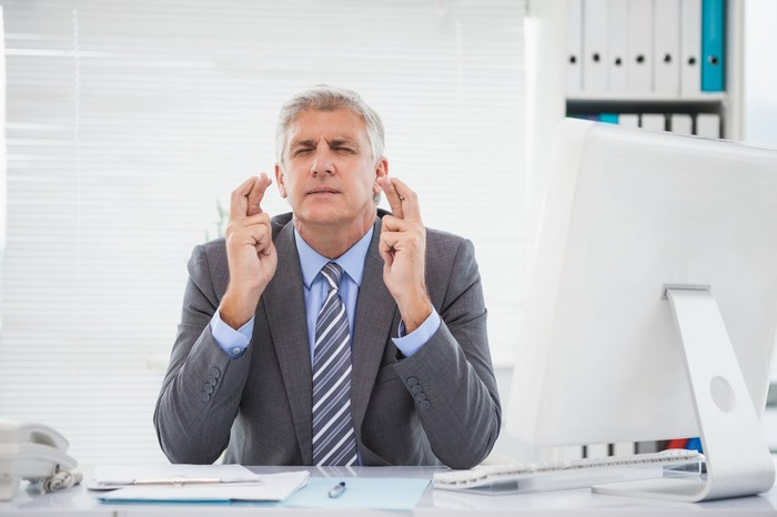 Businessman sitting at desk with computer, crossing his fingers hard with his eyes closed.