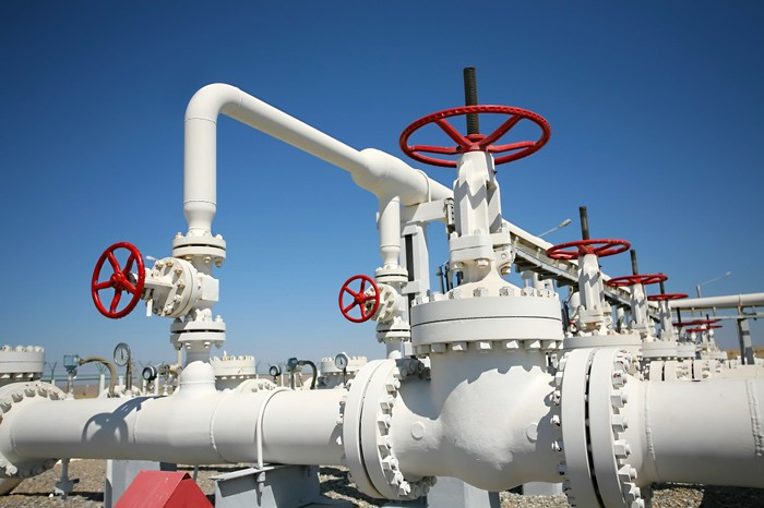 I set of white oil pipelines connecting with red knobs to operate valves.