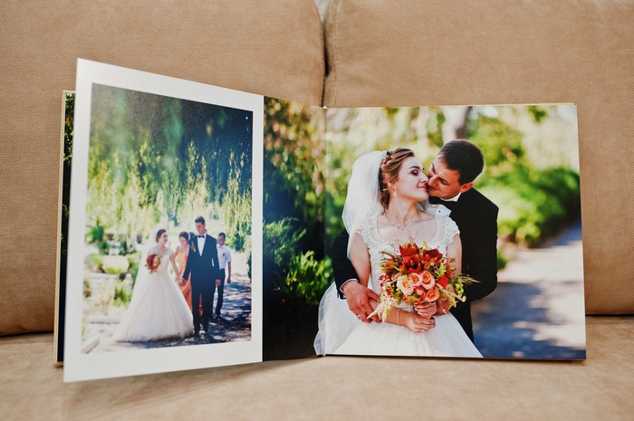 A wedding photo book open showing two pictures of the bride and groom.