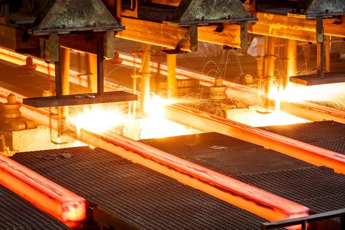 Hot steel on conveyor in steel mill.