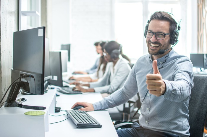 Call center representative sitting at computer, giving a thumbs-up