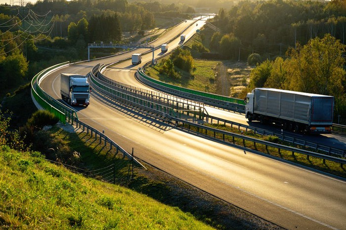 Freight trucks on a European highway at dusk.