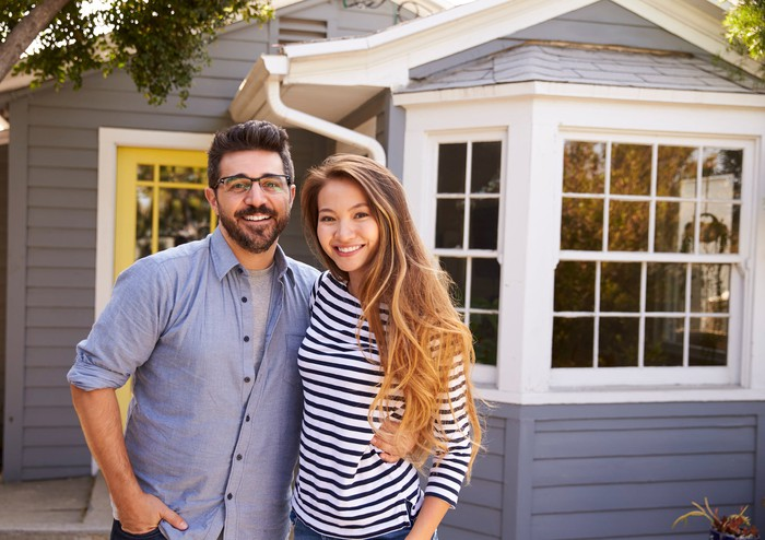 A young couple stands in front of their home.