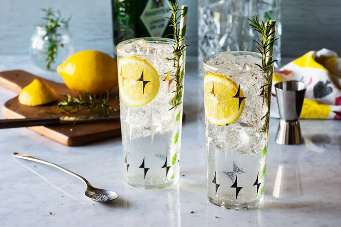 Two glasses with clear liquid and lemons sit on a counter with a lemon on a cutting board in the background.