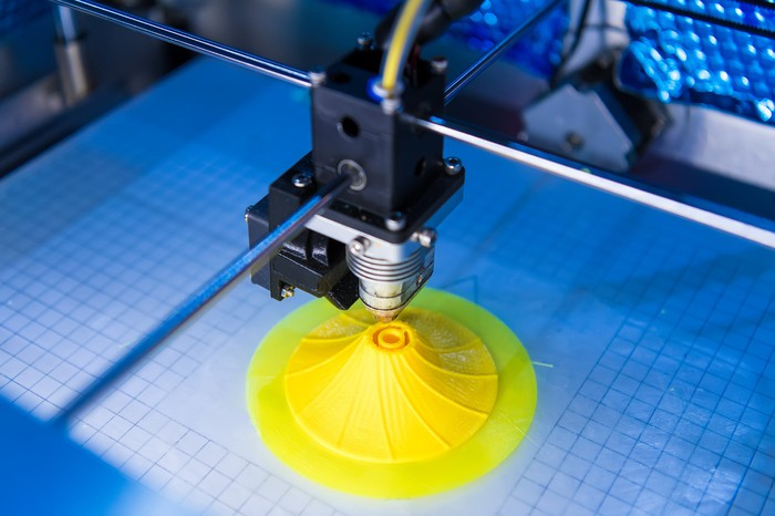 A 3D printer printing a yellow plastic object on a blue surface.