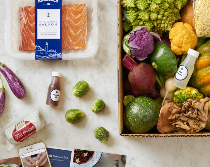 A sample Blue Apron meal kit, featuring salmon, vegetables and seasonings.