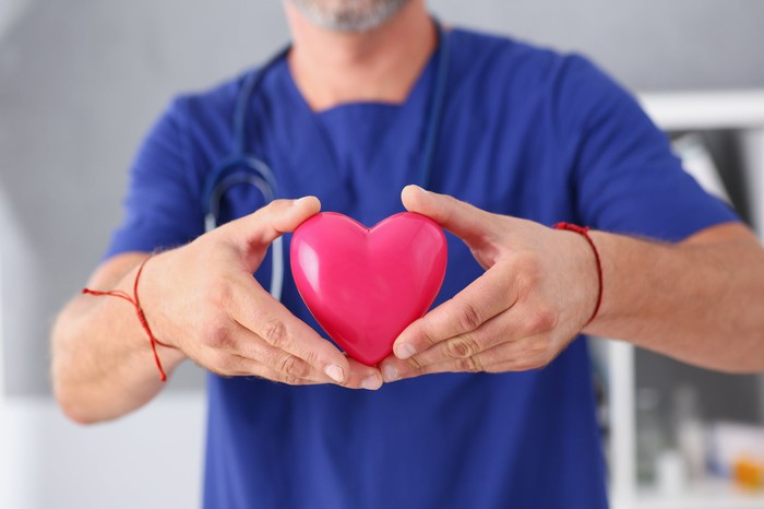 Doctor holding a heart symbol in his hands