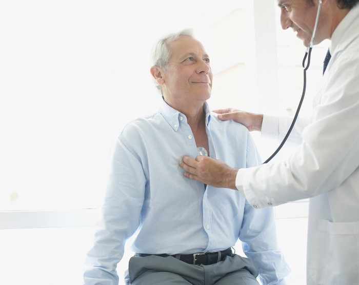 Doctor holding stethoscope to chest of senior man.