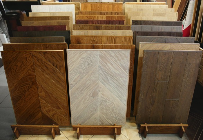Three rows of different types of hardwood flooring displayed in store.