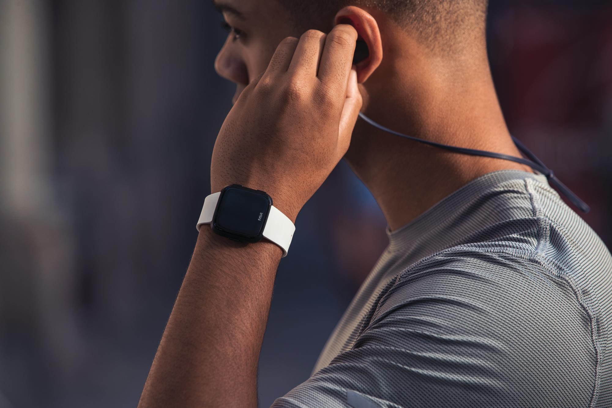 Man in workout gear wearing a Fitbit Versa Smartwatch