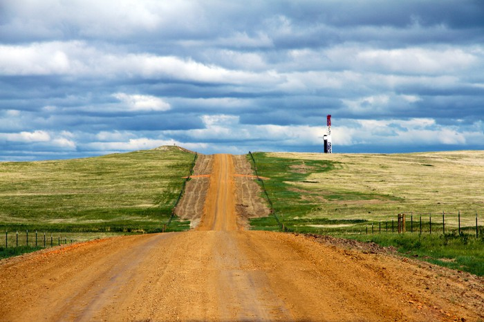 A dirt road leading up to a drilling rig that's over the hill.