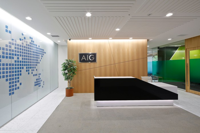 Lobby of an office with stylized world map, modern furnishings, and AIG logo on the wall.