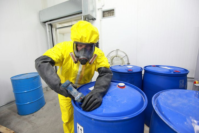 A person fastening a barrel containing chemical wastes.