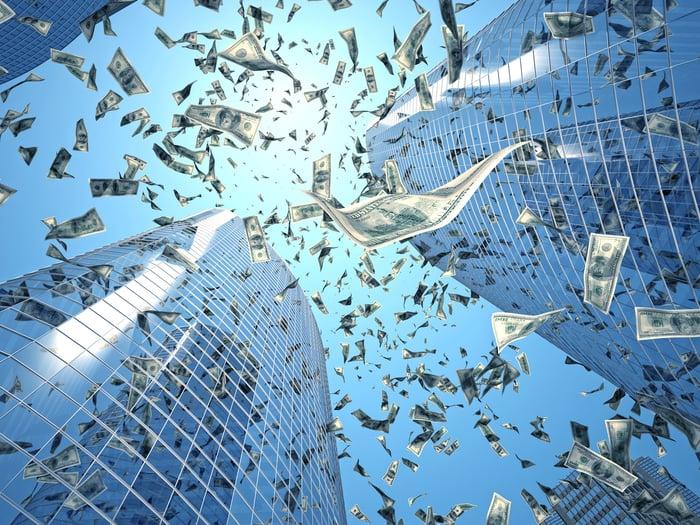 U.S. Dollar bills falling from the sky in between skyscrapers.