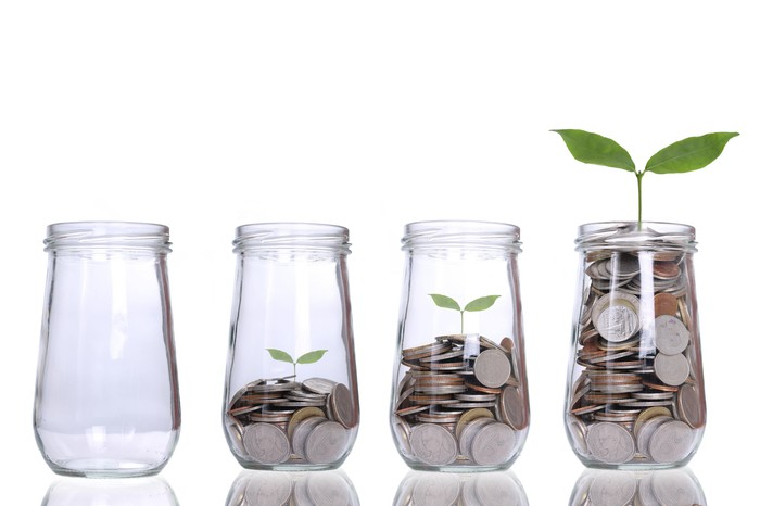 A row of glass jars increasingly filled with coins. A plant grows out of the jar holding the most coins.