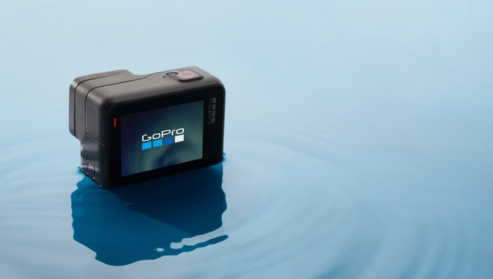 GoPro HERO camera sitting in shallow blue water