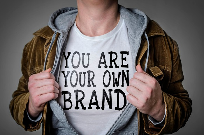 A man wears a shirt that says you are your own personal brand.