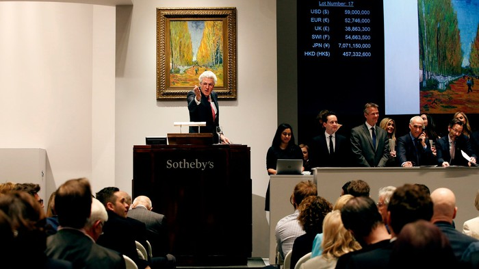 Auctioneer at podium pointing to bidder in audience with various officials at the front and a painting in the background.