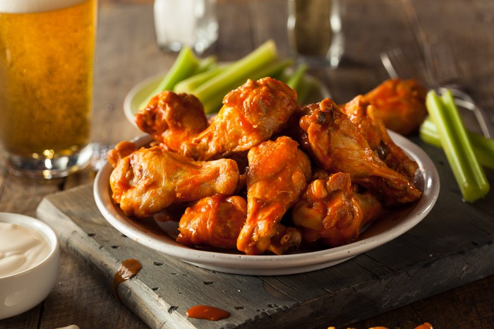 Plate of buffalo chicken wings with beer in the background