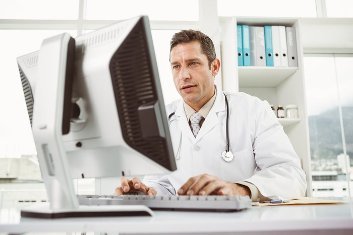Male doctor working at a computer