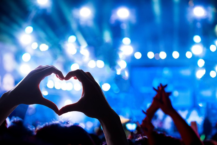 A brigthly lit rock concert, seen from the audience. Up close, one fan's hands form a heart sign.