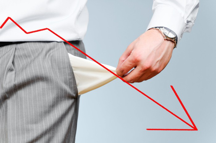 Man turning out his empty pants pocket with a downward trending red arrow in the forefront.