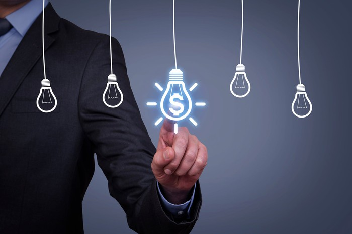 Man pointing to drawing of light bulb with dollar sign with other drawings of light bulbs without dollar sign
