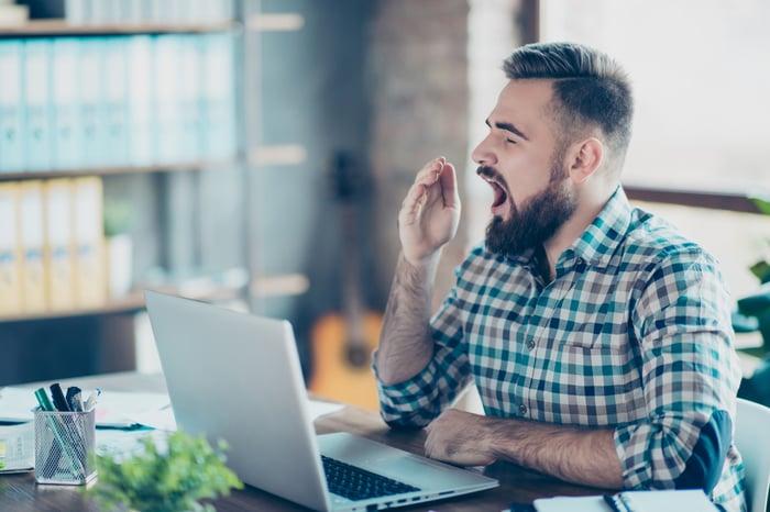 Man looking at laptop and yawning.