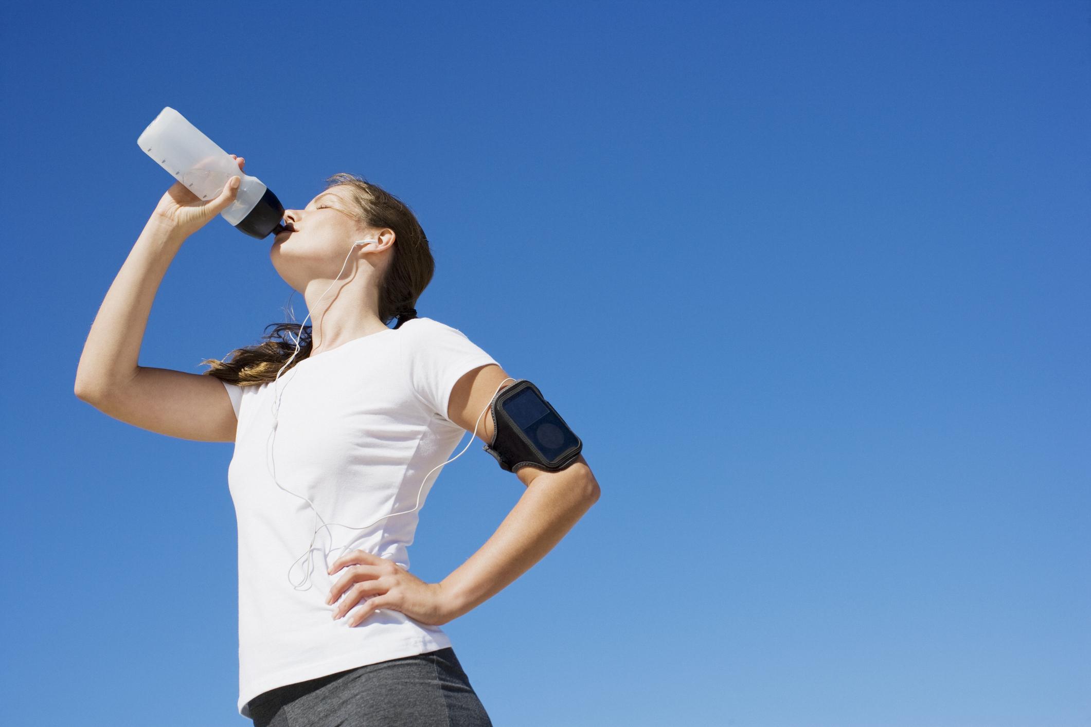 Woman in athletic wear drinking from a water bottle.