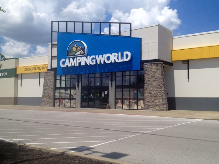 Outside storefront of a Camping World location, with empty parking lot and partly cloudy sky shown.