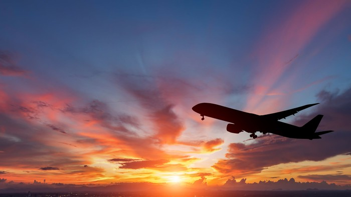 Silhouette of a passenger airplane against a colorful sunset.