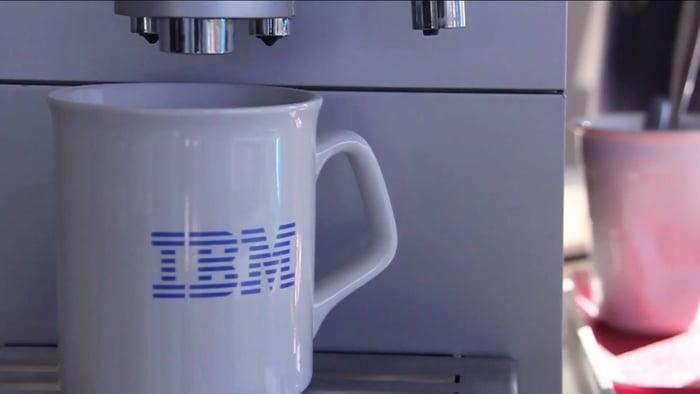 White coffee mug with blue IBM logo on it under an espresso machine.