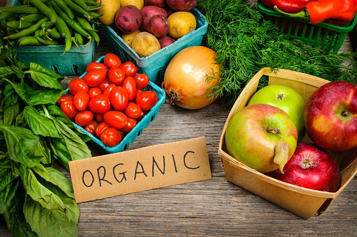 """Assorted fruit and vegetable on a table with a label that says """"organic."""""""