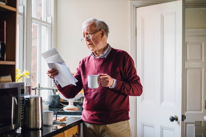 Senior man in a burgundy sweater holding a mug while reading paper bills