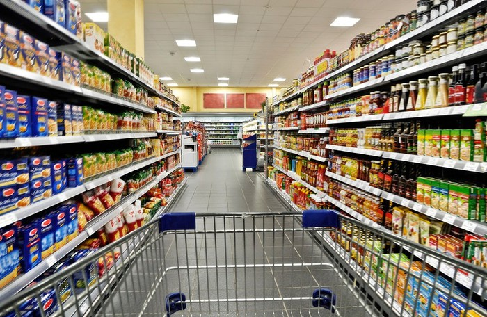 A shopping cart in a supermarket aisle surrounded by packaged foods.