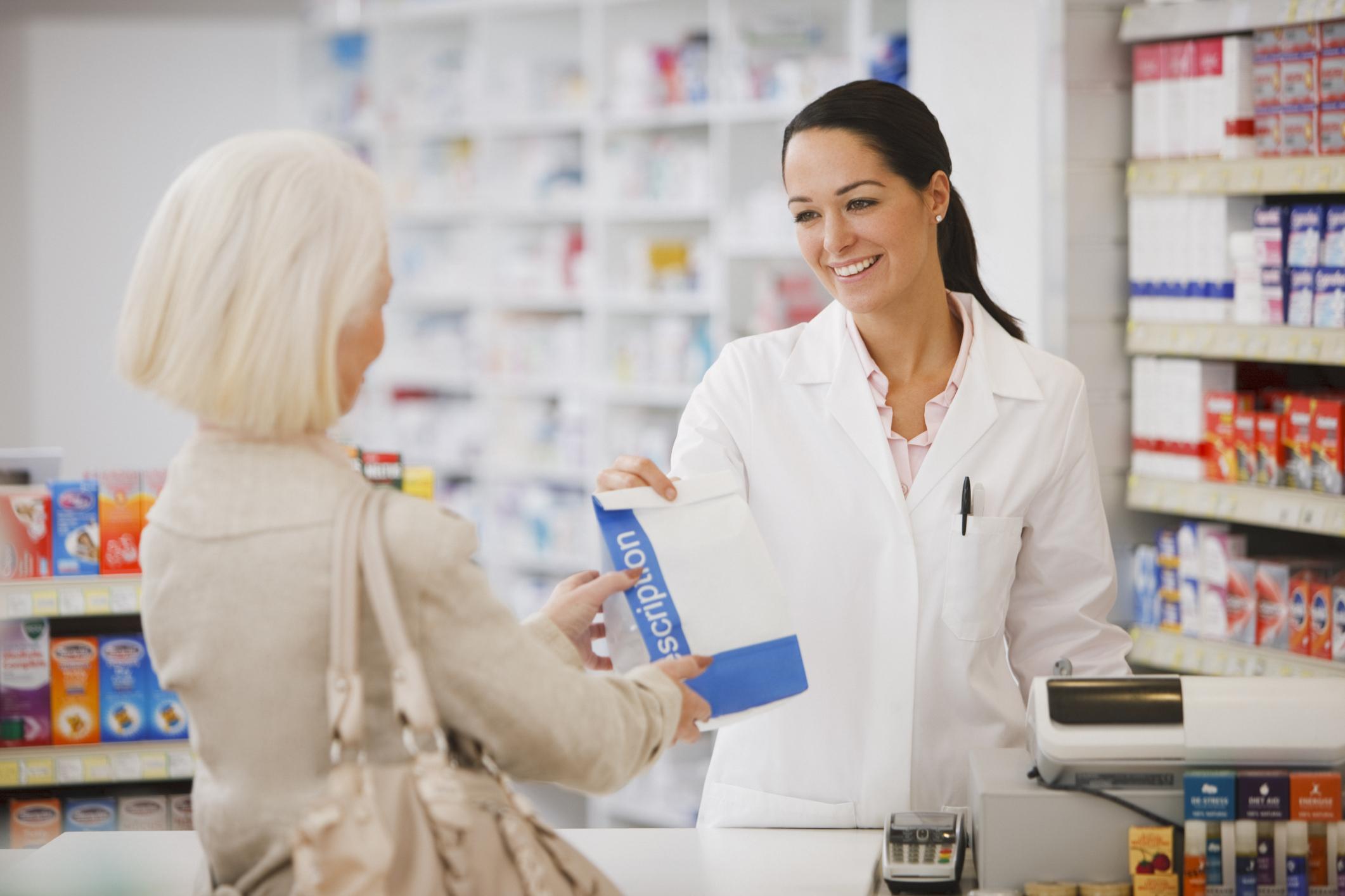 Female pharmacist hands female customer prescribed drugs