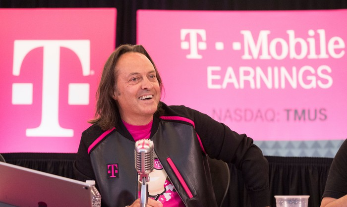 T-Mobile CEO John Legere smiling behind a microphone with a screen over his shoulder that says T Mobile earnings.