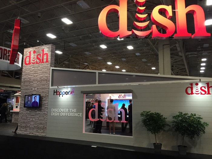 Convention hall with display for DISH, with corporate logo on the side of a mock house and window showing television display.