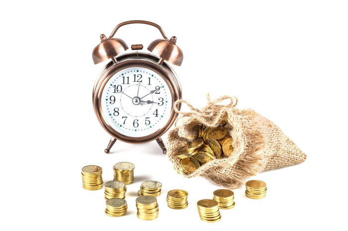 A clock next to a bag of gold coins.