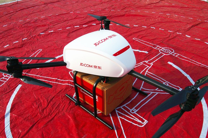 A delivery drone marked with JD's colors and logo, cradles a large cardboard box on a red tarp.