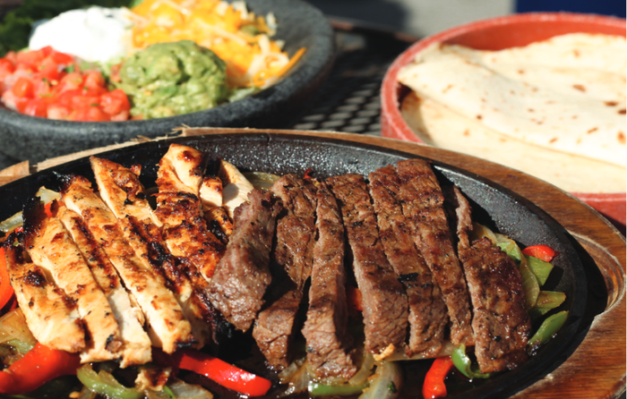 Steak and chicken fajitas on an iron skillet, with tortillas, salsa, cheese, guacamole, and sour cream on the side.