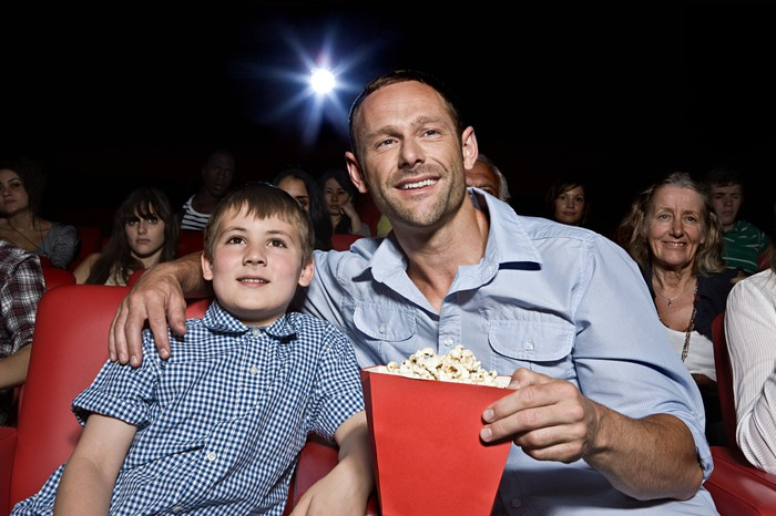 a father and son watch a movie in a theater with popcorn.