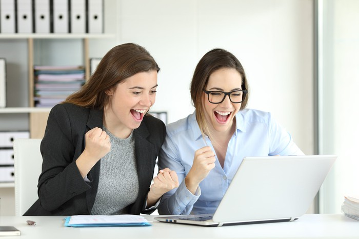 Two smiling woman pumping their right fists looking at a laptop screen