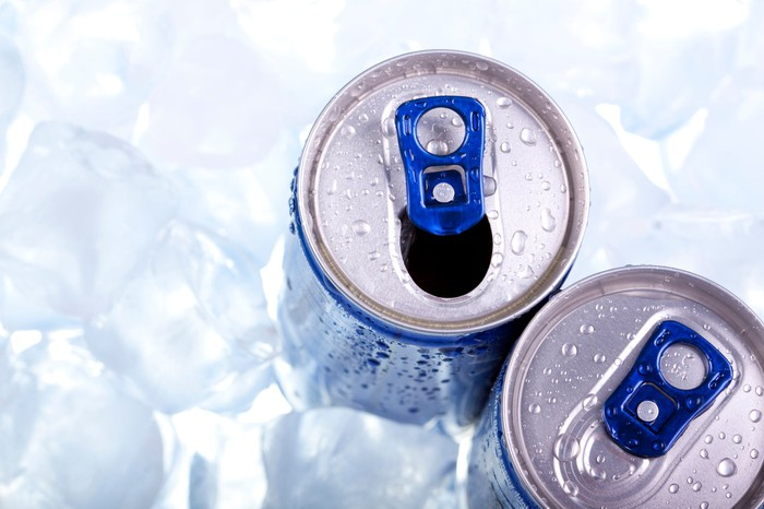 Two energy drinks sitting on ice.