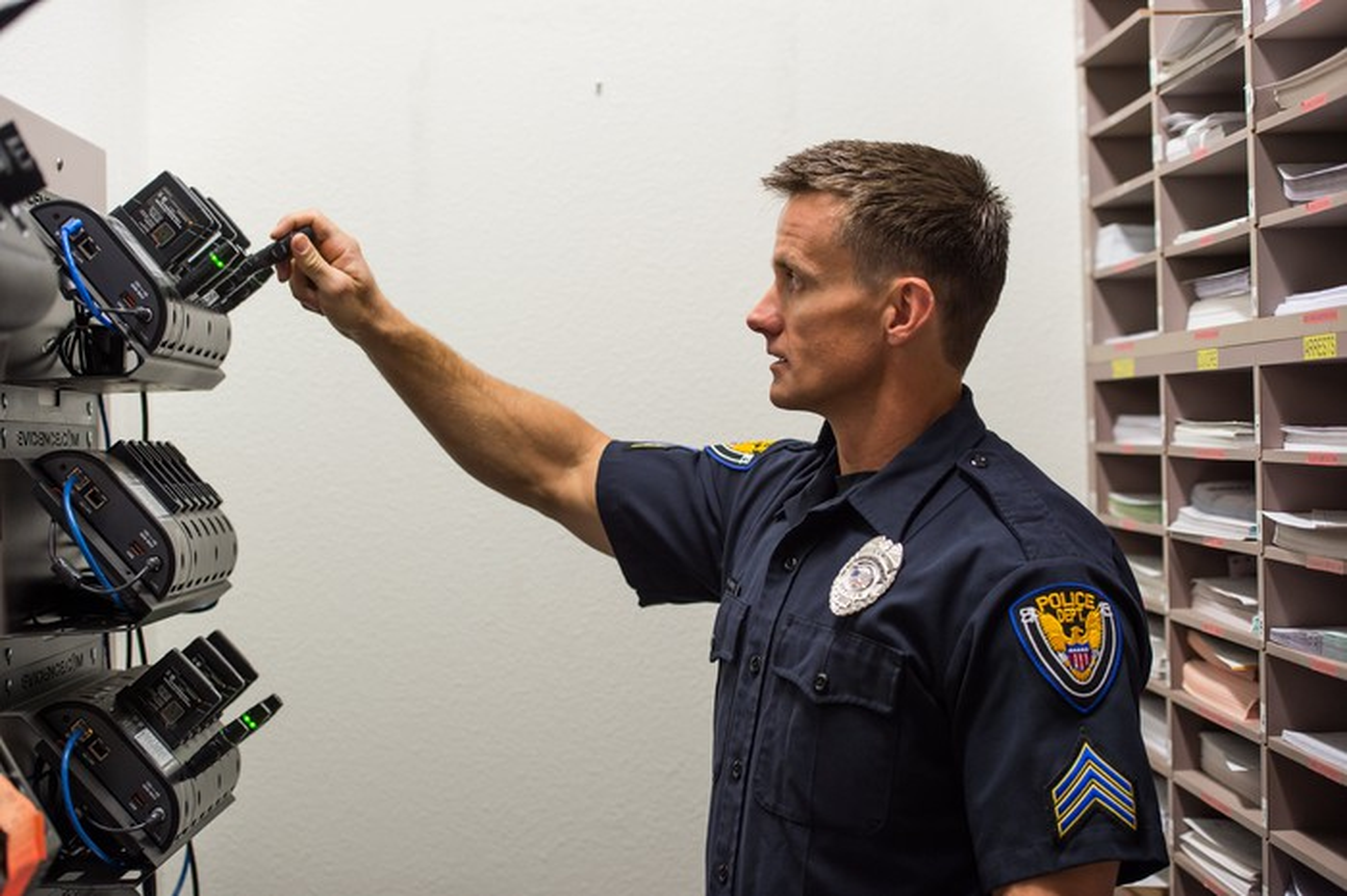 A man in a police uniform putting a body camera in a dock.