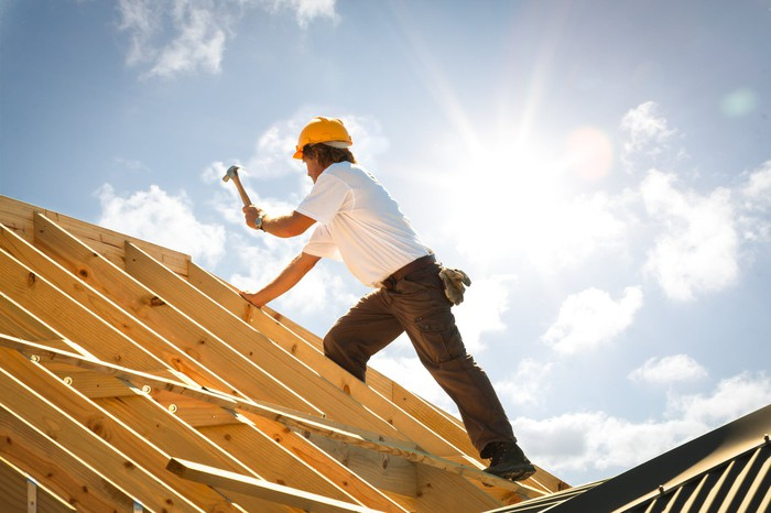 Construction worker hammering a roof